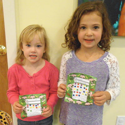 Lily and Ava stopped by to place more stickers on their charts. They'll be picking prizes soon!